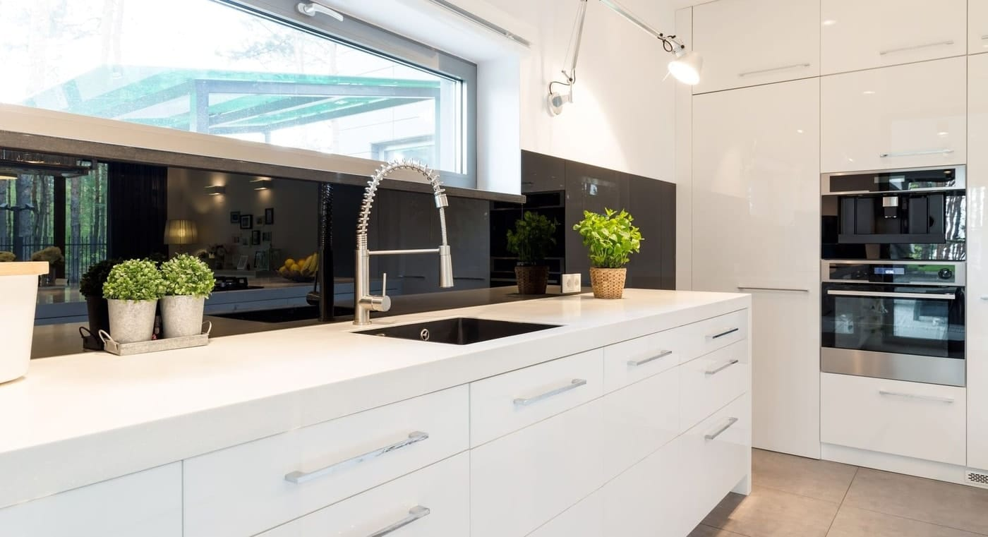 A modern kitchen with silver extendable silver tapware, white counter top, wall mounted oven, and large white storage spaces.