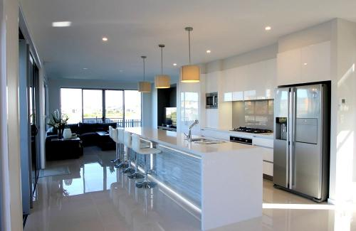 A modern kitchen design with stainless steel appliance and sparkling white benchtop.