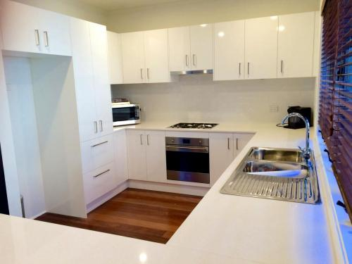 A kitchen with white storage spaces, white counter top, and a gas stove with oven.