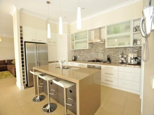 A kitchen with white counter top, beige bench top and a large stainless steel fridge.