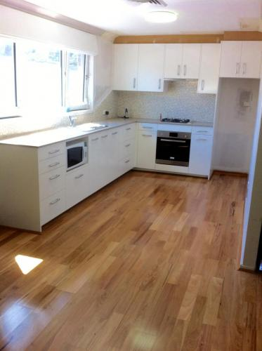 White kitchen renovated from scratch contrasting on timber flooring.