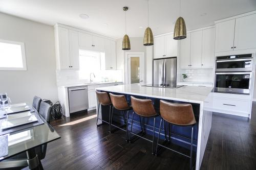 A renovated white kitchen with silver stainless steel appliances.